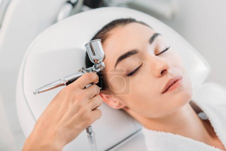 attractive woman receiving facial treatment in spa center