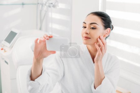 Photo for Woman in white bathrobe taking selfie on smartphone in spa salon - Royalty Free Image