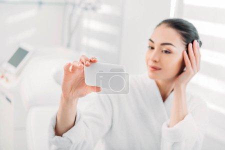 woman in white bathrobe taking selfie on smartphone in spa salon