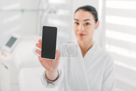 woman in white bathrobe showing smartphone with blank screen in spa salon