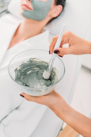 selective focus of cosmetologist with clay mask in bowl and brush in spa salon