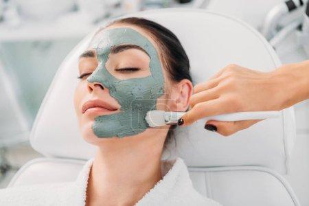 vista parcial del cosmetólogo aplicando máscara de arcilla en la cara femenina en el salón de spa