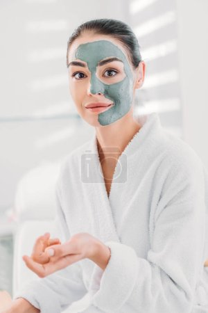 portrait of beautiful woman with clay mask on face in white bathrobe in spa salon