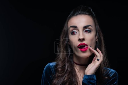 vampire woman touching her tongue isolated on black