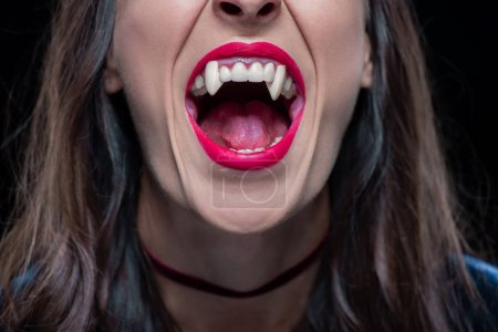 cropped view of woman showing vampire fangs isolated on black