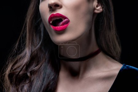 cropped view of sexy vampire woman licking her lips isolated on black