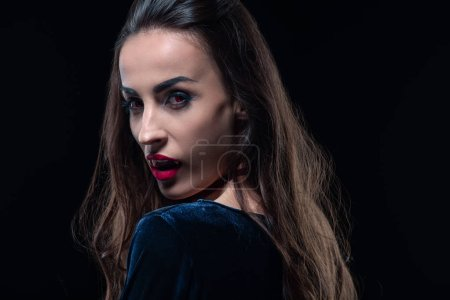 vampire with red lips looking at camera isolated on black