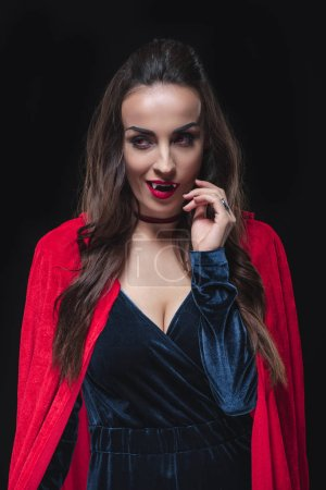 Photo for Sexy vampire woman in red cloak isolated on black - Royalty Free Image
