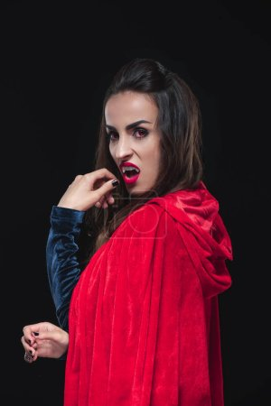 dreadful vampire woman in red cloak showing her teeth isolated on black