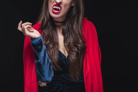 cropped view of vampire woman in red cloak showing her fangs isolated on black