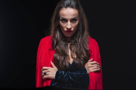 Photo for Grim vampire woman in red cloak looking at camera isolated on black - Royalty Free Image