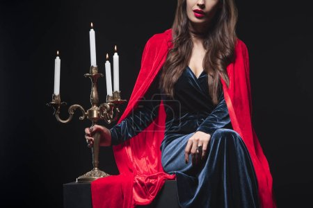 cropped view of woman in red cloak holding candelabrum isolated on black