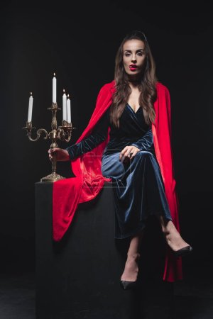 Beautiful vampire in red cloak licking teeth and holding antique candelabrum isolated on black