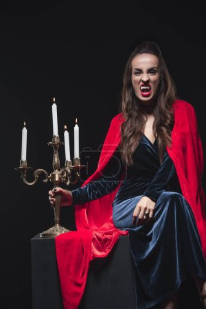 Photo for Dreadful woman in red cloak holding vintage candelabrum and showing vampire teeth isolated on black - Royalty Free Image