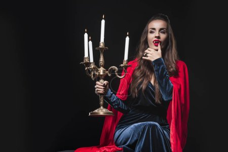 evil woman in red cloak holding retro candelabrum and licking her fingers isolated on black