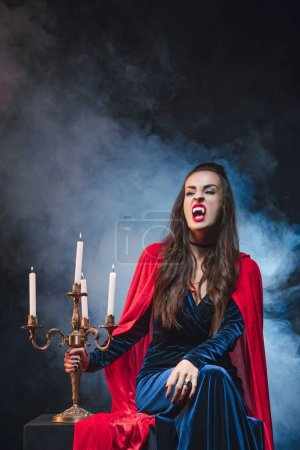 Photo for Woman in vampire costume holding vintage candelabrum on darkness with smoke - Royalty Free Image