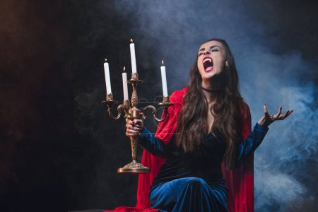 Photo for Woman in red cloak holding vintage candelabrum and showing vampire fangs on dark background with smoke - Royalty Free Image