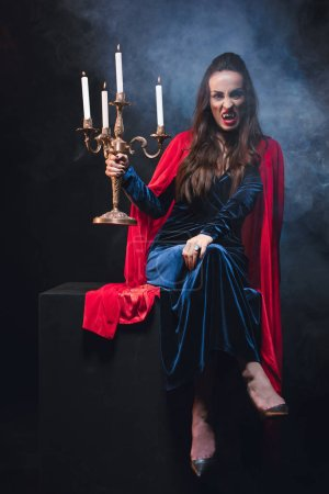 beautiful woman in red cloak holding retro candelabrum and showing vampire teeth on dark background with smoke