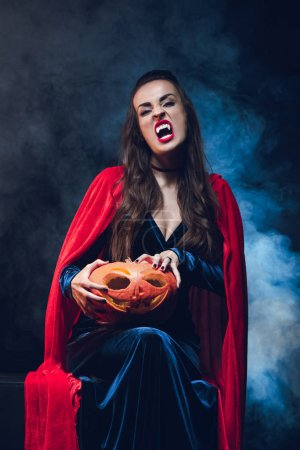 Photo for Woman in vampire costume holding jack o lantern on darkness with smoke - Royalty Free Image