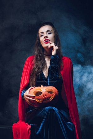 Photo for Attractive woman in vampire costume holding jack o lantern on darkness with smoke - Royalty Free Image