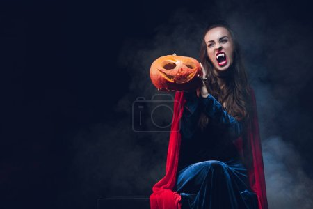 Photo for Woman in vampire costume holding pumpkin on dark background with smoke - Royalty Free Image