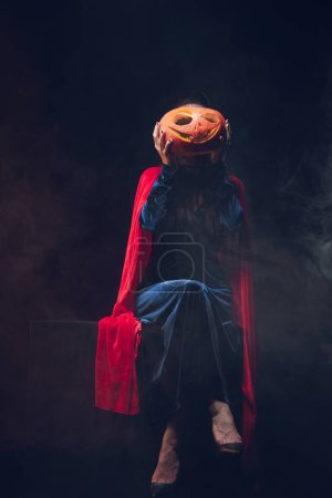 woman in red cloak holding jack o lantern in front of face on dark background with smoke