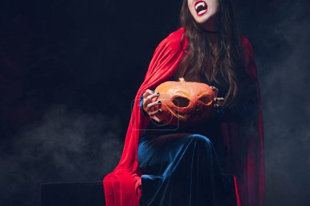 cropped view of beautiful woman in vampire costume holding pumpkin on darkness with smoke