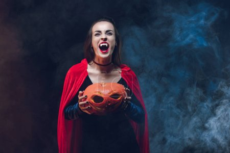 Photo for Mystic woman in vampire costume holding jack o lantern on dark background with smoke - Royalty Free Image