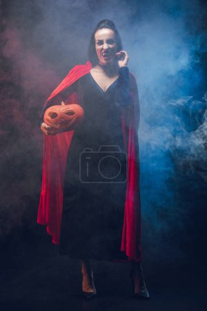 Photo for Attractive woman in vampire costume holding pumpkin on dark background with smoke - Royalty Free Image