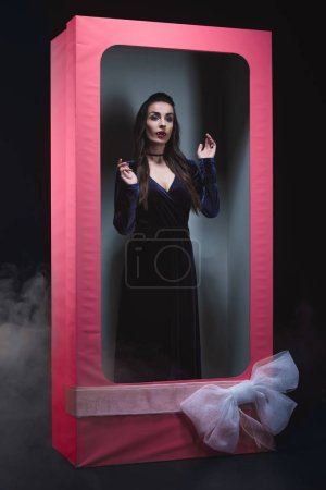 mystic vamp woman posing in doll box with bow