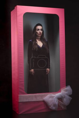 gothic woman in pink doll box witn bow