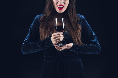Photo for Cropped view of vampire holding wineglass with blood isolated on black - Royalty Free Image