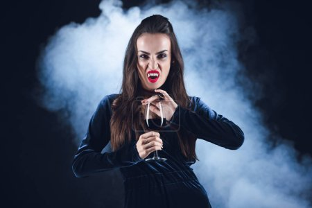 grim vampire holding wineglass with blood on dark background with smoke