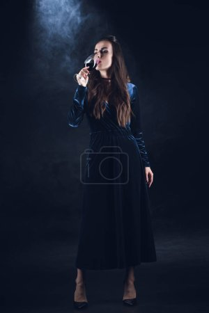 vampire woman drinking blood from wineglass on dark background with smoke