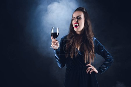 dreadful vampire holding wineglass with blood on dark background with smoke
