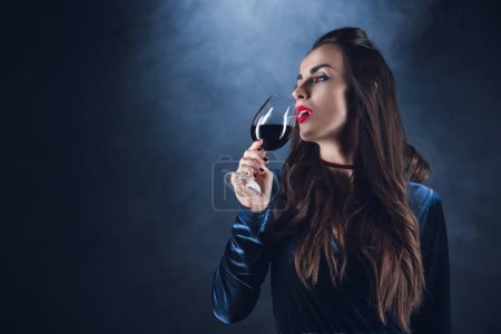 Photo for Beautiful vampire drinking blood from wineglass on dark background with smoke - Royalty Free Image