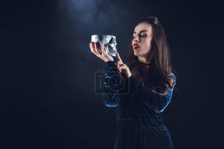 beautiful vampire holding metal skull on dark background with smoke
