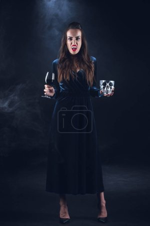 vampire woman holding skull and wineglass with blood on dark background with smoke