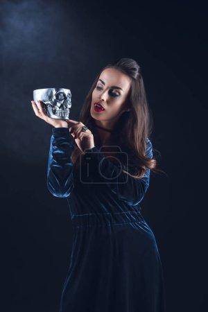 vampire woman holding metal skull on dark background with smoke