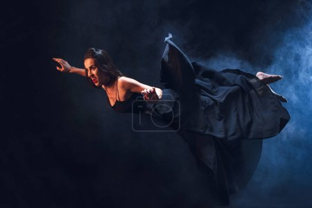 Photo for Grim woman in vampire costume flying on darkness with smoke - Royalty Free Image