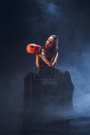 dreadful woman in vampire costume holding jack o lantern on dark background with smoke