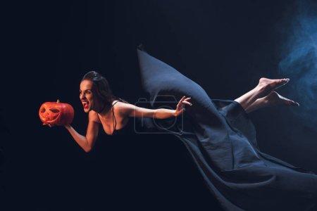 Kobieta w stroju wampira gospodarstwa jack o lantern i pływające w ciemności z dymu