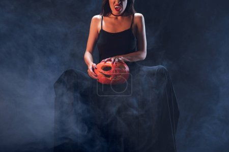 cropped view of woman in vampire costume holding jack o lantern on darkness with smoke