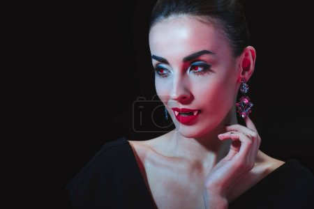 sexy vampire woman showing her fands and looking away isolated on black