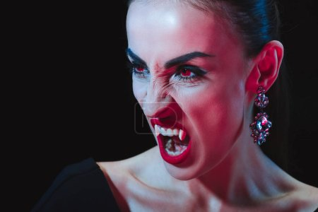 Photo for Dreadful vampire showing her fangs and looking away isolated on black - Royalty Free Image