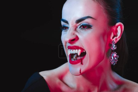 Photo for Vampire showing her fangs and looking away isolated on black - Royalty Free Image