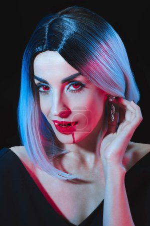 sexy vampire woman looking at camera isolated on black