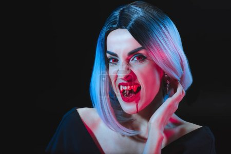 Photo for Dreadful woman showing vampire teeth isolated on black - Royalty Free Image