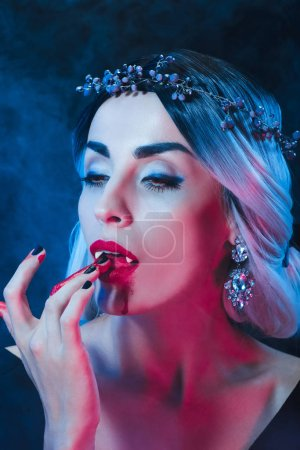 Photo for Sexy vampire woman licking blood from fingers on dark background with smoke - Royalty Free Image