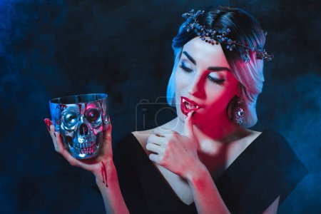 Photo for Beautiful vampire woman holding metal skull with blood and licking her fingers isolated on black - Royalty Free Image